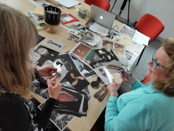 participants cutting out photos of artefacts from Stromness Museum collection, ready to bring them to life.