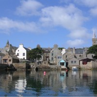 Stromness from the sea showing the houses huddled together along the harbour. Image credit: Creative commons